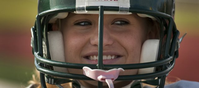 With her full gear on for practice, Amanda Moyer smiles underneath her helmet with pink mouth guard attached. The Free State senior has joined the football team as a walk-on starting field goal kicker.