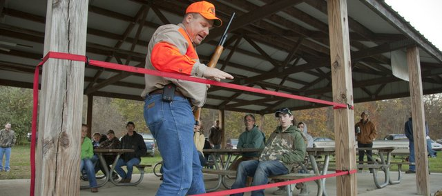 Hunter instructor Derek Welsh uses a simulated fence to demonstrate proper handling of a firearm when hunting alone during a hunter education class Saturday.