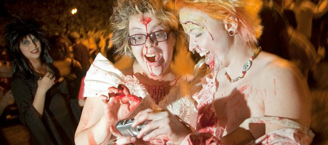 "Mike Yoder/Journal-World Photo.Bleeding zombie brides Devon Masqua, left, and Briana Lambert, review photographs on their camera during the 4th annual Lawrence Zombie Walk earlier this month. Because of the dimming light I used my flash to illuminate the foreground subjects and a longer shutter-speed to maintain some of the surrounding ambient light. The long shutter-speed also added some nice ""ghosting"" movement to the two women."