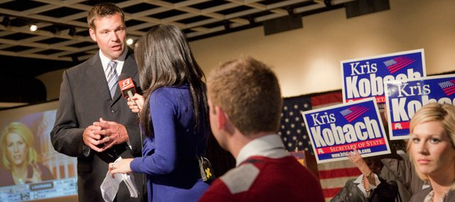 Kris Kobach, left, visits with a T.V. news reporter during a GOP Clean Sweep party Tuesday, Nov. 2, 2010 in Toepka. Kobach defeated Chris Biggs in the race for Sec. of State.