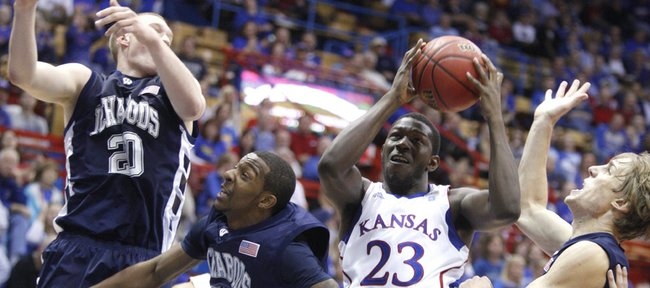 Kansas forward Mario Little pulls a rebound away from Washburn defenders Bobby Chipman (20), Nate Daniels (33) and Logan Stutz, right, in the second half of the exhibition game, Tuesday, Nov. 2, 2010 at Allen Fieldhouse.