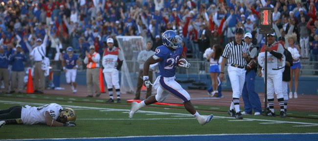 The Memorial Stadium crowd rises up as Kansas running back James Sims leaves Colorado linebacker Liloa Nobriga on the ground for a touchdown late in the fourth quarter, Saturday, Nov. 6, 2010 at Kivisto Field. The extra point by Jacob Branstetter tied the game.