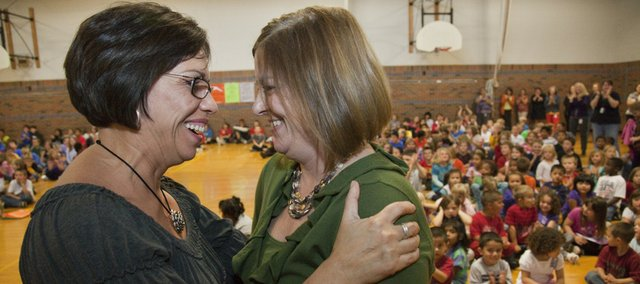 Kennedy School team leader Ann Lounsbury, right, gets a hug from Principal Cris Anderson Tuesday after being recognized as the 2010-11 Lawrence Master Teacher during a school assembly in the gym. Lounsbury now will be the district's nominee for Kansas Master Teacher, sponsored by Emporia State University's Teachers College.