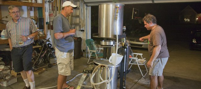 The brewing structure  holds three large kettles that can easily transfer the mixed brew from one kettle to another. It is designed to hook to a portable propane tank that creates the heat needed for the water. On a recent evening, neighbors Larry Palmquist, left, and David Conway helped John Pepin, right, with a batch in the garage.