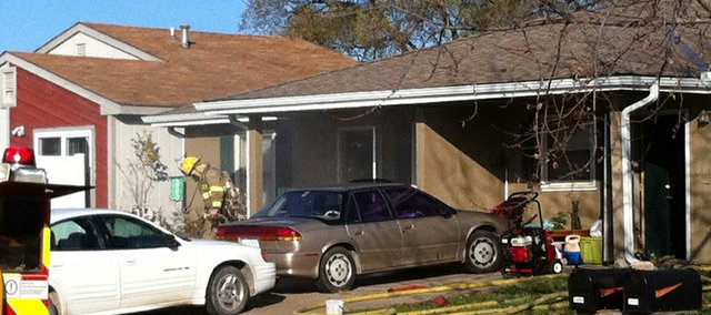 Smoke from a fire drifts into the street while emergency crews search a duplex in the 1300 block of E. 25th Terrace just after 9 a.m. on Tuesday, Nov. 16, 2010.