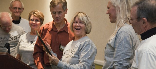 Linda Klinker, center, reacts to the weight of the Service to Mankind Award she received Tuesday from the the Lawrence Sertoma Club during a reception at the Springhill Suites. Klinker is chair of the board of directors for Cans for the Community, which has raised thousands of dollars for local nonprofit organizations. Other members of the group watch, from left: Will Lunn, Delmer Kruse, Mona McManigal, Delisa Drewes and Wendell McGaugh. Two other group members honored were Linda Lang and Kathy Richardson.