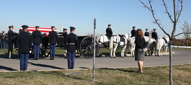 Members of the Arlington National Cemetery honor guard finish transferring the flag-draped casket of Army Spc. Thomas A. Moffitt, of Wichita, onto a caisson to be taken to his grave one-third of a mile away. Moffitt, who was killed Oct. 24 during an insurgent attack in Afghanstian, was laid to rest in Section 60 of the national cemetery during a Nov. 12 service will full military honors.