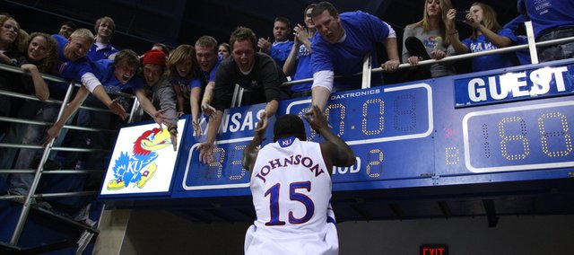Jayhawk fans above the 93-60 final score receive a flying high five from Kansas guard Elijah Johnson following their win over North Texas Friday, Nov 19, 2010 at Allen Fieldhouse.
