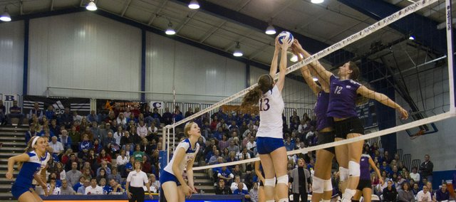 Nicole Tate (13) fights for the ball against two Wildcat blockers during KU's game against Kansas State Wednesday evening in the Horejsi Center. Kansas State jumped out to a 2-0 lead before KU evened the score at 2-2.  However, the Wildcats were too strong on the final set and defeated the Jawhawks and spoiled Senior Night for KU's four graduating seniors.