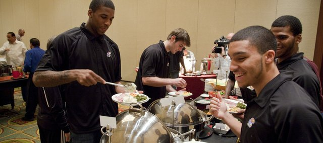 Kansas players, clockwise from left, Thomas Robinson, Conner Teahan, Royce Woolridge and Niko Roberts prepare their plates during the team's Thanksgiving meal Thursday at the Renaissance Hotel in Las Vegas.
