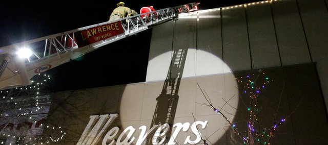 Santa is rescued from the rooftop at Weaver's Friday by Lawrence Fire and Medical. The holiday season officially kicked off Friday night as the Christmas lights along Massachusetts Street were switched on.