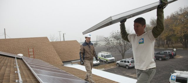 Chris Rogge, left, director of solar design with Cromwell Environmental, and Nick Gardner, installer, mount several solar panels on the roof of the Douglas County Extension Office building in this November 2010 file photo. The units will supply about 15 percent of the building's energy and will also be used for educational purposes.