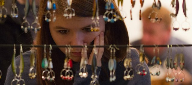 Josie Benz, 15, Charlotte, N.C., examines earrings made from fishing lures at the Bizarre Bazaar on Saturday at the Lawrence Arts Center. The event featured plenty of arts and crafts for sale and live music.