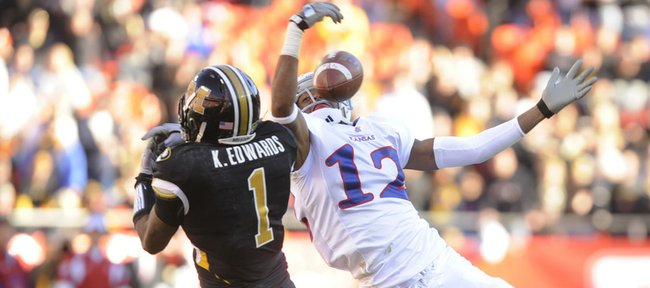 Kansas' Christian Matthews (12) goes up for a pass against Missouri's Kip Edwards (1). Kansas and Missouri met at Arrowhead Stadium Saturday for the 119th game in the rivalry series.