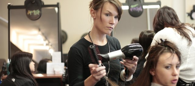 Emily Metzger of Lawrence, a student at Z Hair Academy, 2429 Iowa, styles the hair of client Amber Long, Lawrence, on Nov. 16. Metzger will graduate in December. Trade schools and businesses such as Z Hair Academy provide instruction and experience that can help jump-start careers.