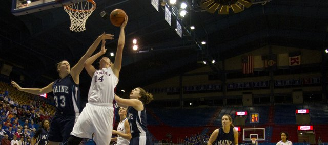 Kansas center Krysten Boogaard (14) shoots a reverse layup around Maine forward Ali Nalivaika (33) during their game Wednesday night at Allen Fieldhouse. The Jayhawks put on an impressive offensive display, setting a school record by scoring 126 points, and easily defeated the Black Bears 126 – 63.