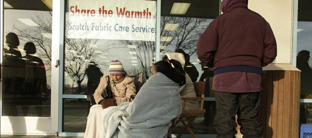 A crowd forms early outside the I-70 Business Center, where Lawrence residents gathered to try and secure a winter coat. Scotch Dry Cleaners collected and cleaned the coats as part of its Share the Warmth campaign.