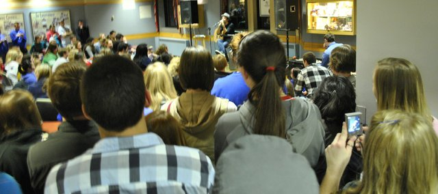 People watch and listen as musician Jason Mraz performs in the Kansas Union Friday, Dec. 3, 2010. The impromptu concert was not advertised until right before it began.
