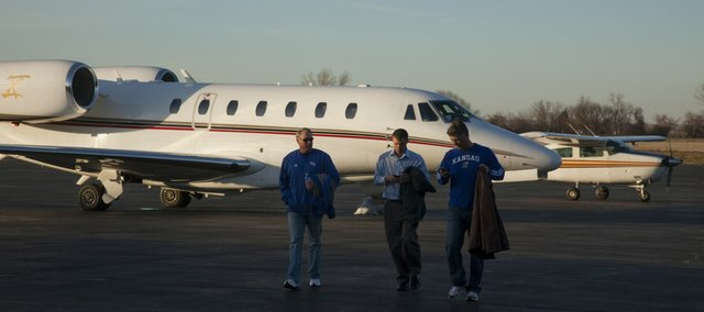 Visitors, from left, Roy Jackson, Joel Murphy and Dax Gaskill walk to the terminal after flying their Cessna plane two hours from Hugoton to catch a Kansas University men's basketball game last week. Lawrence Municipal Airport north of the Kansas River has been providing air transport services for years.