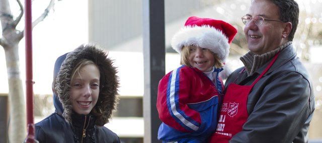 Abby Wagner, 11, Lawrence, rings a bell as her father Scott holds her sister Ava, 4, outside of Weaver's Saturday, Dec. 4, 2010 in downtown Lawrence. The family was collecting donations for the Salvation Army.