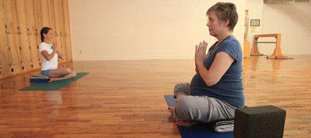 Kim Lacy, left, instructor with Yoga Center of Lawrence, 920 Mass., warms up along with Lisa Dahlm 43, Lawrence, during a prenatal yoga class.