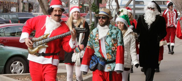 a crowd of Santas gathers in downtown Lawrence on Saturday for Lawrence's first ever SantaCon. Starting at The Sandbar, Santas and other holiday characters made their way from bar to bar collecting donations for the Just Food pantry in Lawrence.