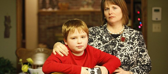 Nine-year-old Walker Koberlein is pictured with his mother, Kelli Koberlein, at their Lawrence home. Walker and his mother were both patted down by security agents after the camera he is holding set off a chemical detector while going through screening. While many parents themselves are willing to participate in security screenings, some are concerned with allowing their children to go through the various processes.
