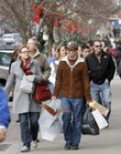 Alicia Kaufman, left, and Tyler Conway, right, both of Lawrence, carry shopping bags with gifts during an afternoon of shopping in downtown Lawrence, Saturday, Dec. 18, 2010. Considered one of the busiest shopping days of the holiday season, many shoppers in Lawrence had to plan their shopping time either before or after the home KU men's basketball game at 11 a.m. Saturday.