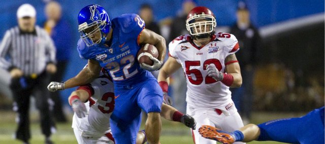 Boise State running back Doug Martin is brought down by Utah's Chaz Walker (32) and Matt Martinez (52) during the the first half of the Maaco Bowl NCAA college football game , Wednesday Dec. 22, 2010, in Las Vegas.