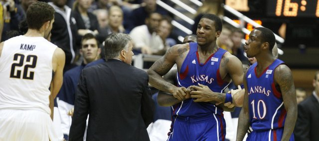 Kansas forward Thomas Robinson tries to break free from being restrained after tempers flared against Cal during the second half as Tyshawn Taylor (10) and Cal's Harper Camp (22) hang out on the periphery.
