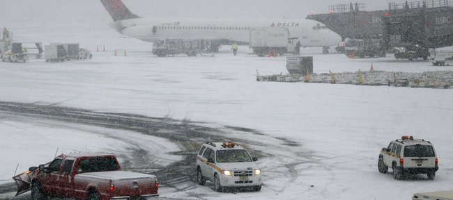 A Delta plane is seen at Newark Liberty International Airport during a snow storm Dec. 26, 2010, in Newark, N.J. Airlines are working to rebook stranded passengers and possibly add flights after a winter storm on the East Coast caused thousands of flight cancellations and left countless passengers stranded. Kansas University's Tyshawn Taylor was among the Jersey travelers snowbound Sunday.