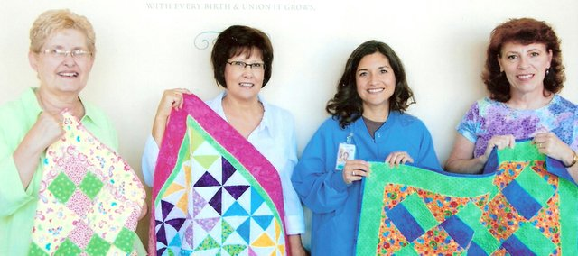 Pieces members, along with Denise Martinek, director of the LMH Family Birthing Center, display some of the quilts they have made. From left: Beth Reynolds, Marla Welch, Martinek and Shelly Hornbaker.