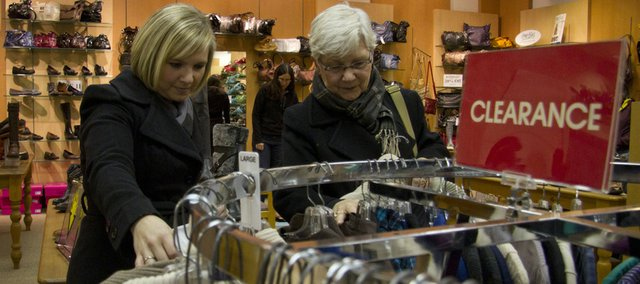 Tracie Howell, left, Lawrence, stops with her mother, Page Massey, Lago Vista, Texas, to browse the sweaters on the clearance rack at Weaver's Department Store in downtown Lawrence. Sales, returns, exchanges and gift cards enticed shoppers back to stores on Sunday.