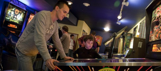Jason Scheffelmaer, Olathe, left, plays a restored Attack From Mars pinball game while Taylor Brownback, 10, Basehor, watches. The two were at a pinball party Saturday, Dec. 4, at Gary Martin's home in Lawrence, where he restores old pinball machines.