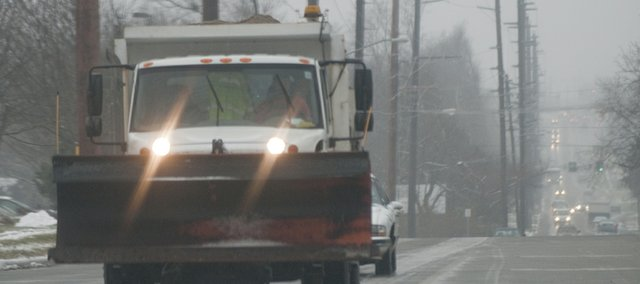 A city public works sand truck travels east on 19th Street on Tuesday morning, spreading sand on intersections during a light sleet.