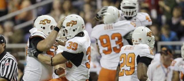 Oklahoma State players celebrate after a fumble recovery in the first quarter. The Cowboys roughed up Arizona, 36-10, on Wednesday night in the Alamo Bowl in San Antonio.