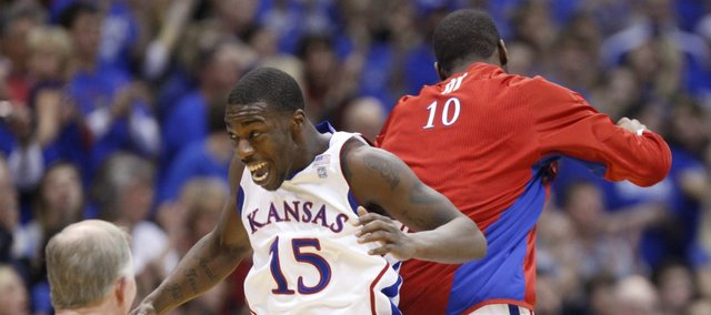 Kansas guard Elijah Johnson (15) gets a flying, celebratory bump from teammate Tyshawn Taylor during a first-half timeout., Wednesday, Dec. 29, 2010 at Allen Fieldhouse.