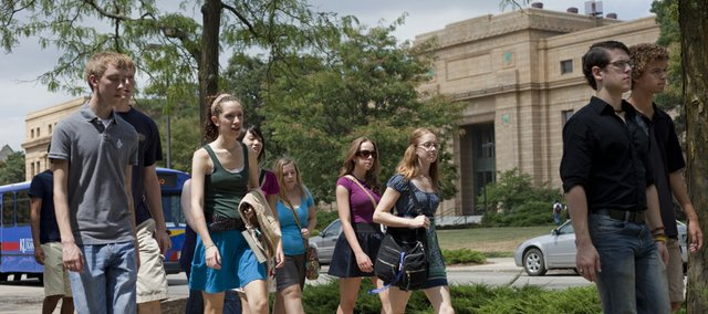 KU students walk across campus the day before classes start for the fall semester. Students participated in campus activities Wednesday that included tours of the libraries, the bus system and campus organization and club information booths.