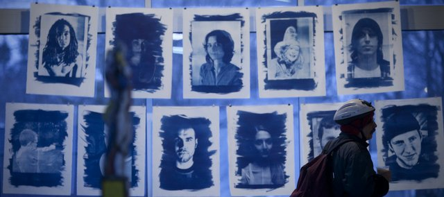 Lawrence resident Douglas Underwood walks by a display of cyanotype contact prints by Kansas University senior Chris Moll, Overland Park, in the gallery space of the Hobbs Taylor Loft building in downtown Lawrence.