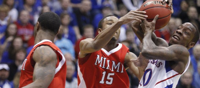 Kansas guard Tyshawn Taylor tangles with Miami (Ohio) University guard Orlando Williams as he drives to the bucket during the first half, Sunday, Jan. 2, 2011 at Allen Fieldhouse.