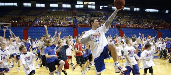 Kansas guard Tyrel Reed helps to lead a group of kids through the fundamentals of how to properly execute a left-handed layup during the Holiday Hoops Clinic on Friday, Dec. 31, 2010, at Allen Fieldhouse.