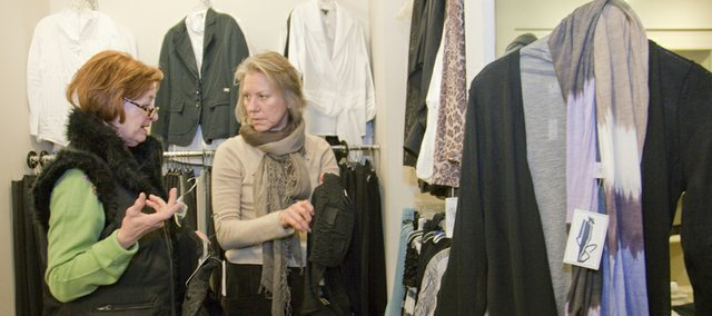 Ann Evans, of Lawrence, left, gets some advice from Kathy Swanson, owner of Spectator's, 710 Mass., while Evans shopped at the women's clothing store Thursday. A new report has found that the city is losing large amounts of sales in the category of women's clothing.