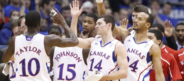 Kansas players Tyrel Reed (14) and Travis Releford (far right) congratulate Tyshawn Taylor during a timeout in the first half against UMKC on Wednesday, Jan. 5, 2011 at Allen Fieldhouse.
