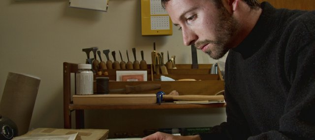 Hagen Miller prepares pages from an 1854 family Bible to be rebound at his home in east Lawrence.