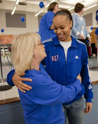Woodlawn Elementary celebrated its National Blue Ribbon School Award Friday at a special assembly.  Third grade teacher Sue Siegfreid, left, got a hug from former Woodlawn student and now KU women's basketball player Tania Jackson.