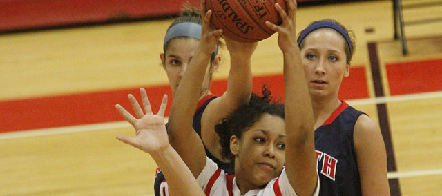 Lawrence High senior Brittany Ray holds the ball high against three Olathe North defenders on Friday night at Lawrence High School. LHS won the game, 48-30.