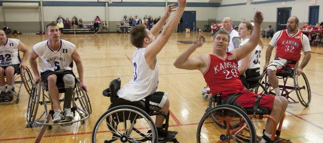 Jarvis Stirn, No. 20, right, a member of the Kansas Wheelhawks basketball team, passes the ball in a game against a Nebraska team Saturday in a wheelchair basketball tournament at Holcom Park Recreation Center. Teammate Jim Kesler, No. 32, of Sabetha, looks on from the perimeter.