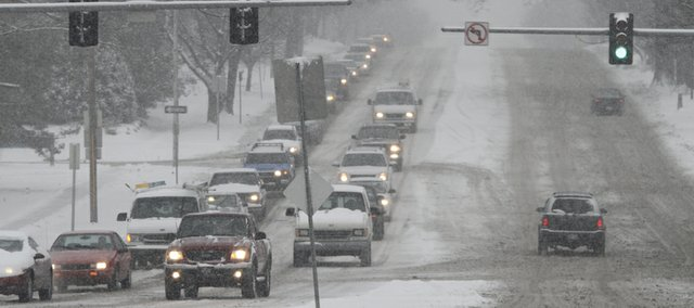 Morning traffic travels east on Sixth Street at Vermont Street on slick roads Jan. 10, 2011 . Lawrence schools closed Monday after several inches of snow fell early in the morning and more was expected throughout the day.