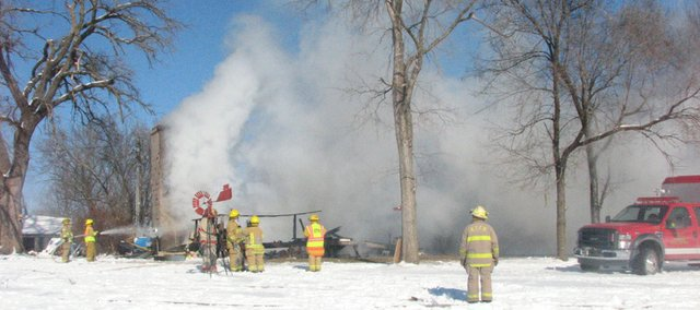 Firefighters attempt to put out a fire in the 21000 block of Cantrell Road northwest of Linwood on Tuesday, Jan. 11, 2011. A portion of the house, which is in Leavenworth County, collapsed during the fire.