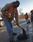 "In this 2010 file photo, Willie Harris, with the Public Works Department, fills a pothole with ""cold patch"" on Iowa Street"